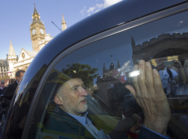 "Newly elected leader of Britain's opposition Labour party, Jeremy Corbyn, passes the Houses of Parliament and Big Ben as he leaves in the back of a taxi after addressing a pro-refugee rally in central London on September 12, 2015. Anti-austerity leftwinger Jeremy Corbyn was elected leader of Britain's opposition Labour Party in a landslide victory that could divide the party and cause headaches for the government on foreign policy. Tens of thousands of Europeans rallied urging solidarity with the huge numbers of refugees entering the continent, as Hungary's populist premier said leaders were ""in a dream world"" about the dangers posed by the influx. AFP PHOTO / JUSTIN TALLIS / AFP PHOTO / JUSTIN TALLIS"